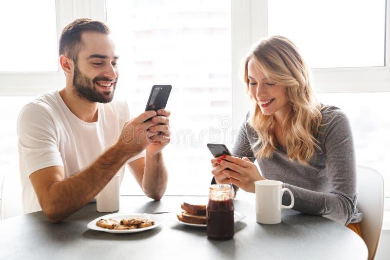Os pares de amor que sentam-se na cozinha têm um café da manhã usando telefones celulares fotografia de stock royalty free