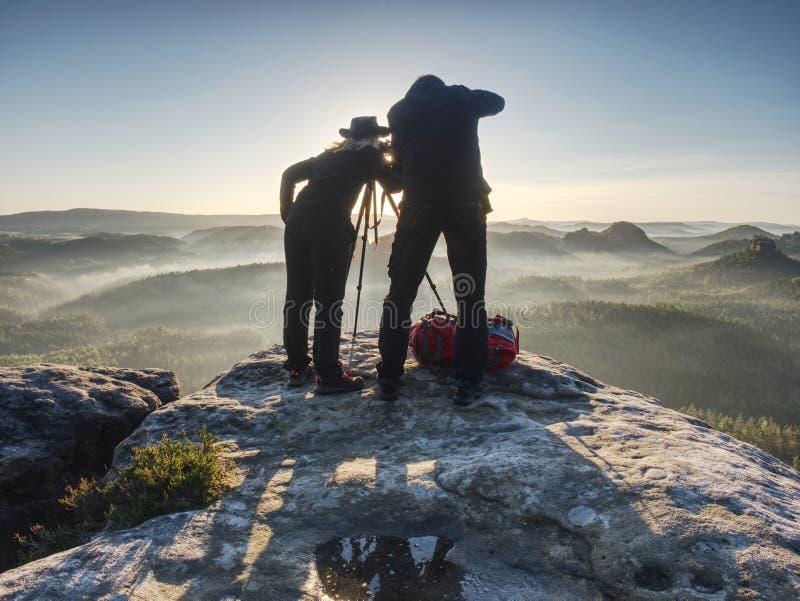 Os pares de artistas criativos trabalham e falam na borda exposta da rocha fotografia de stock royalty free
