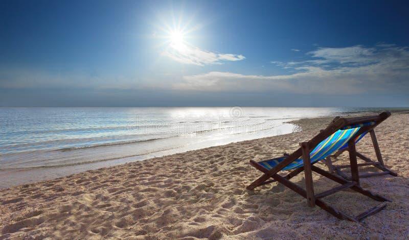 Os pares de cadeiras azuis encalham na praia da areia foto de stock