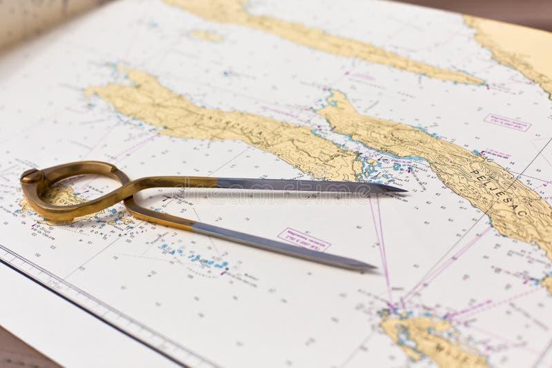 Os pares de compassos para a navegação em um mar traçam fotografia de stock royalty free
