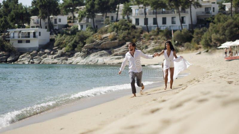Os pares de corrida apenas casados na praia nas horas de verão, dia ensolarado, têm o humor feliz Fundo do Seascape imagem de stock royalty free
