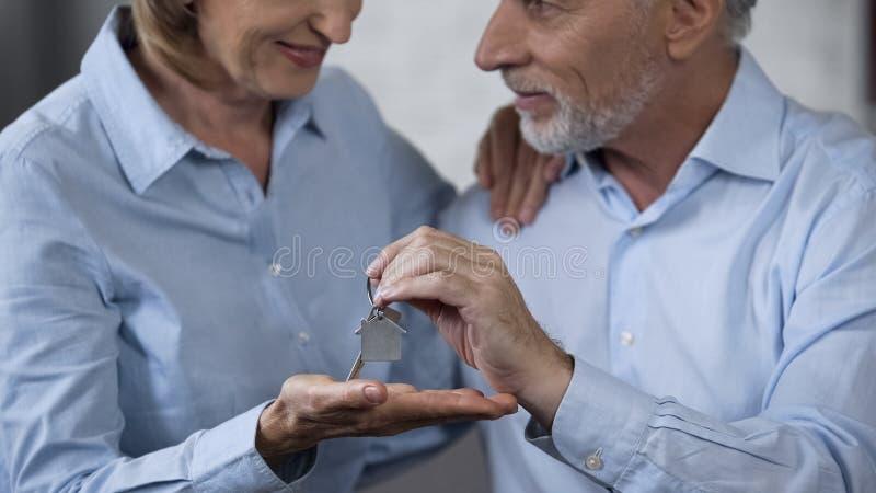 Os pares de envelhecimento felizes que guardam chaves da casa, sonhos vêm verdadeiro, investimento na compra imagens de stock royalty free