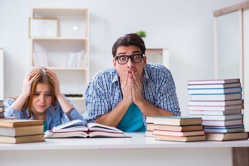 Os pares de estudantes que estudam para exames da universidade imagem de stock