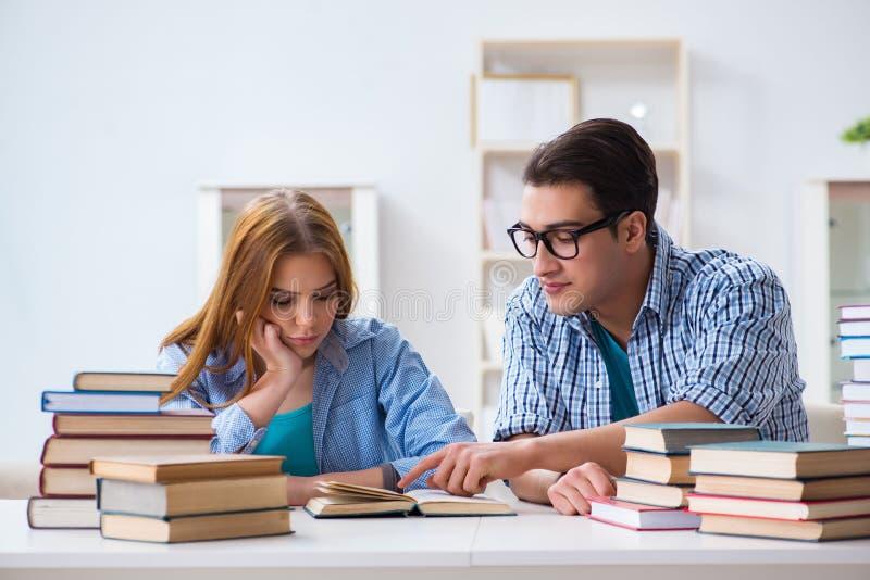 Os pares de estudantes que estudam para exames da universidade imagens de stock