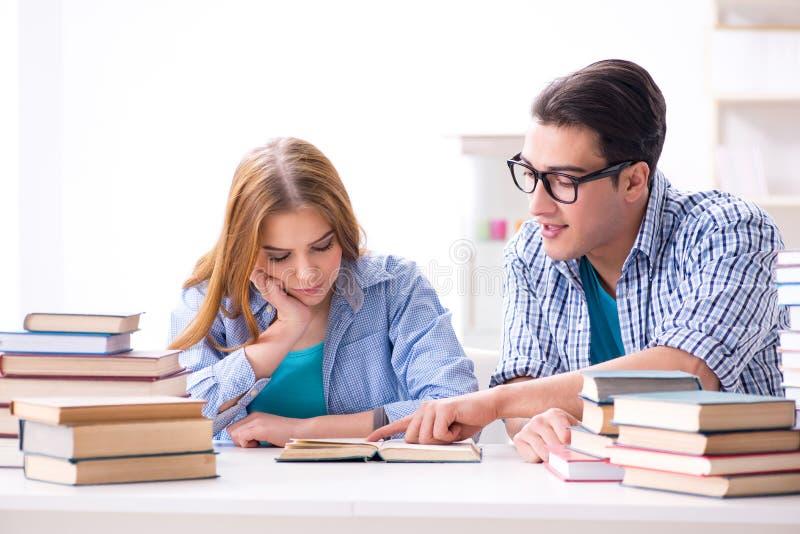 Os pares de estudantes que estudam para exames da universidade fotos de stock royalty free