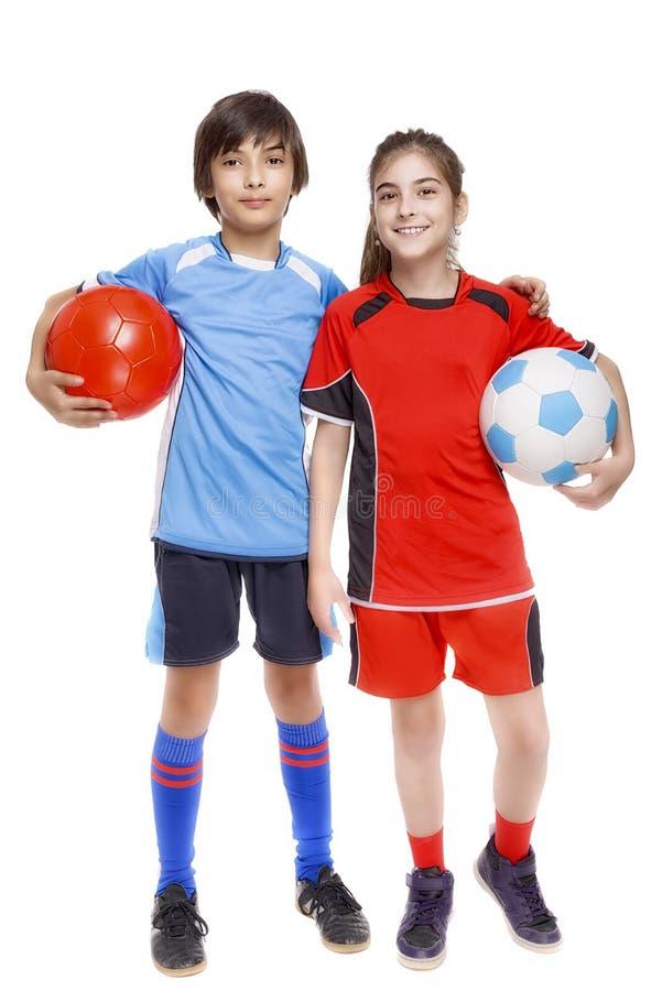 Os pares de menina e de menino vestiram-se no equipamento do futebol fotografia de stock