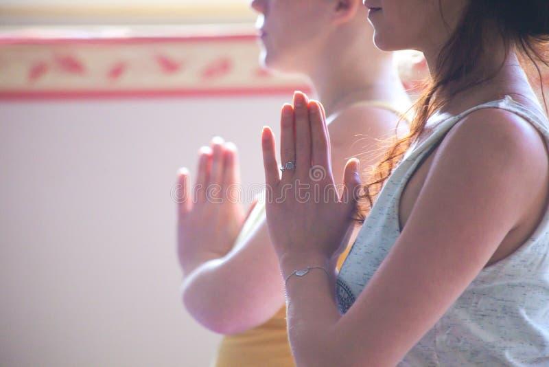 Os pares de mulheres na ioga classificam as mãos no gesto do namaste fotografia de stock royalty free