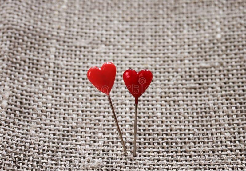 Os pares de pinos afiados sob a forma dos corações vermelhos colaram no áspero fotografia de stock royalty free