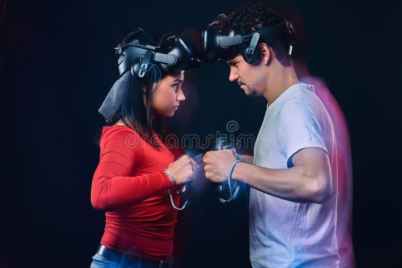 Os pares de pro gamers com auriculares de VR participam na batalha do jogo Foto com efeito da luz fotografia de stock royalty free