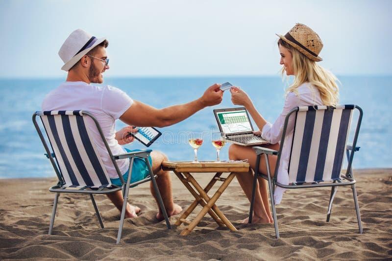 Os pares de sorriso felizes que surfam a rede e apreciam o verão na praia imagem de stock