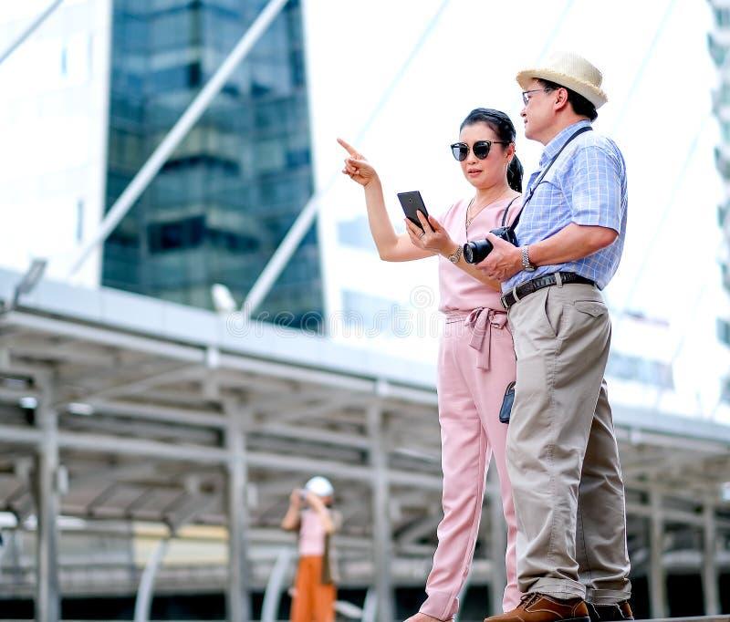 Os pares de turista asiático do ancião e da mulher estão viajando entre a cidade grande e discutem sobre os mapas no telefone cel foto de stock