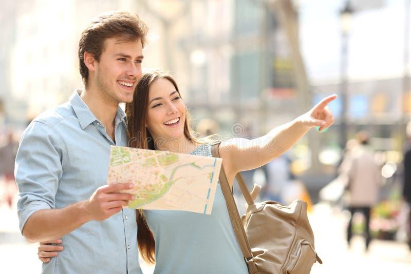 Os pares de turistas que consultam uma cidade guiam a pesquisa de lugar foto de stock royalty free