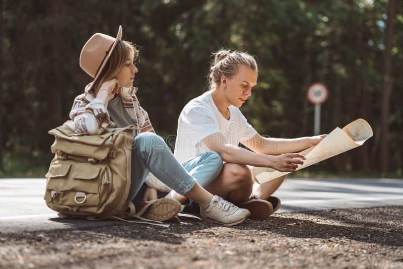 Os pares de viajantes que sentam-se no lado da estrada descansam e olham o mapa de lugar foto de stock royalty free
