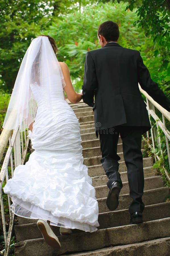 Os pares do casamento andam acima às escadas e as mãos guardarar. backview foto de stock royalty free