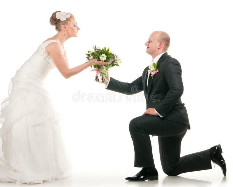 Os pares do casamento estão prendendo o ramalhete nupcial imagens de stock