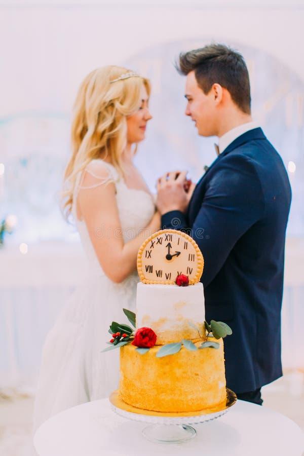 Os pares do casamento olham lovingly se Bolo doce no primeiro plano fotografia de stock royalty free