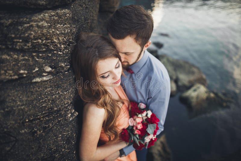 Os pares do casamento que beijam e que abraçam em rochas aproximam o mar azul fotos de stock royalty free