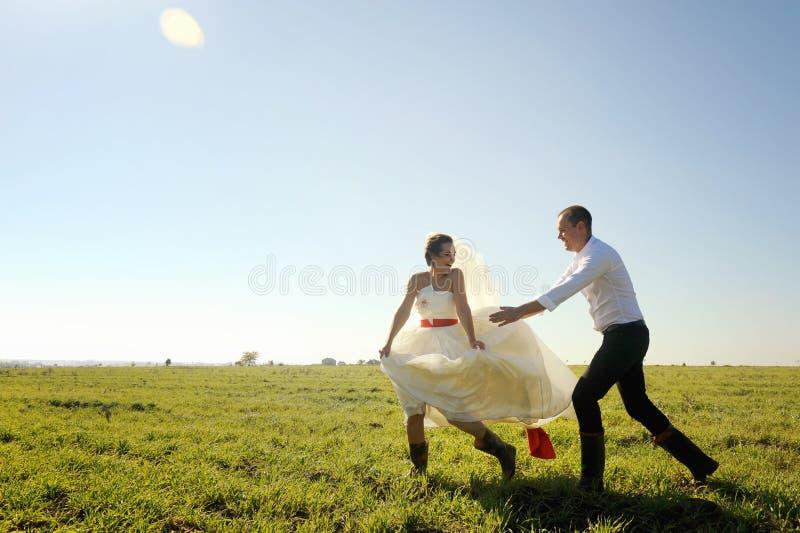 Os pares do casamento têm um divertimento exterior, alcançam um com o otro fotografia de stock