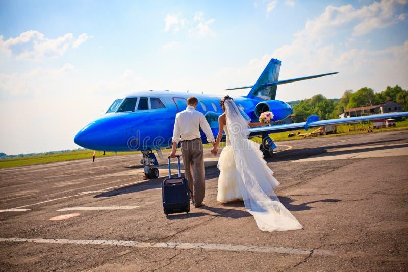Os pares do casamento voam na lua de mel foto de stock