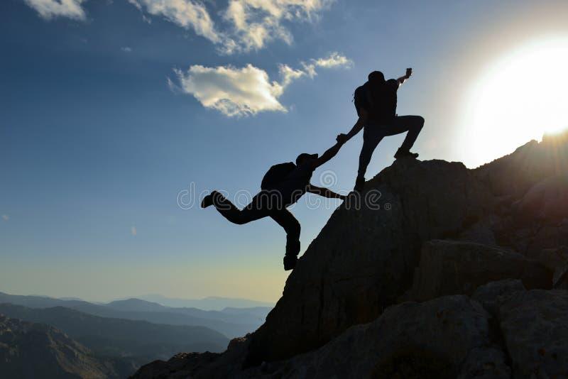 Os pares do homem e da mulher ajudam a silhueta nas montanhas imagem de stock