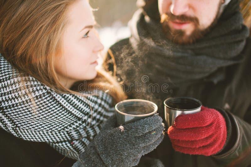 Os pares do moderno no inverno estacionam com chá quente da garrafa térmica fotos de stock royalty free
