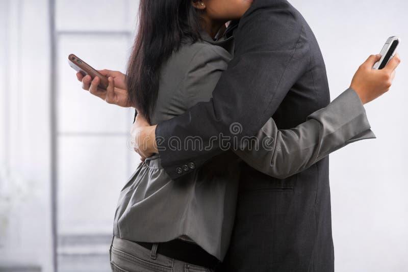 Os pares do negócio abraçam contudo ainda usando o telefone de pilha fotografia de stock