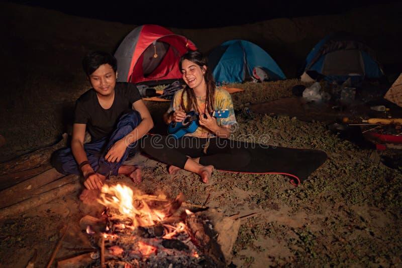 Os pares do retrato que acampam, apreciam a noite com guitarra a para cantar assim a imagem de stock royalty free