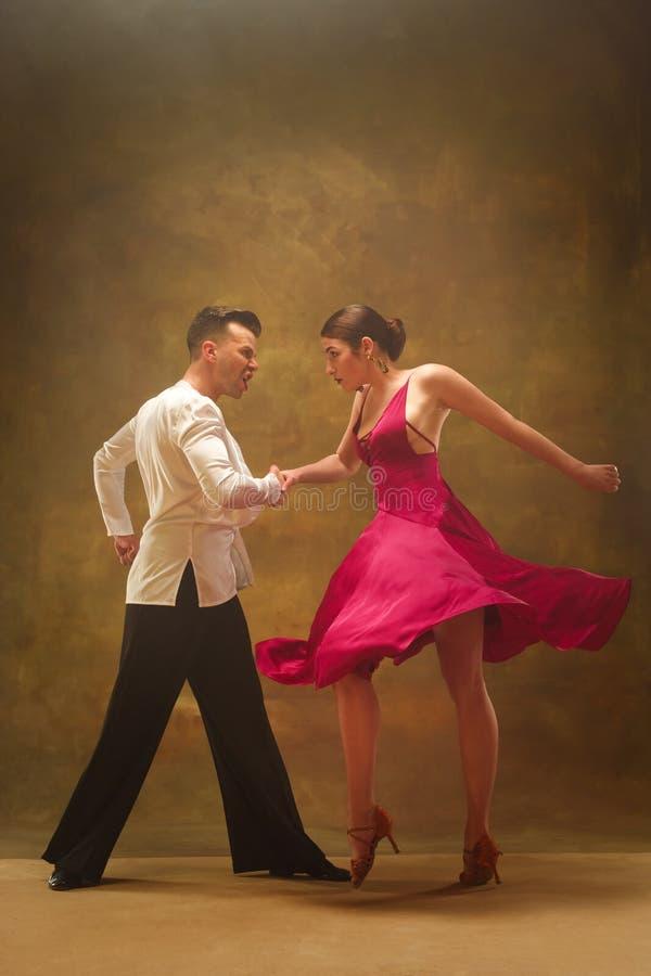 Os pares do salão de baile da dança no ouro vestem a dança no fundo do estúdio imagem de stock