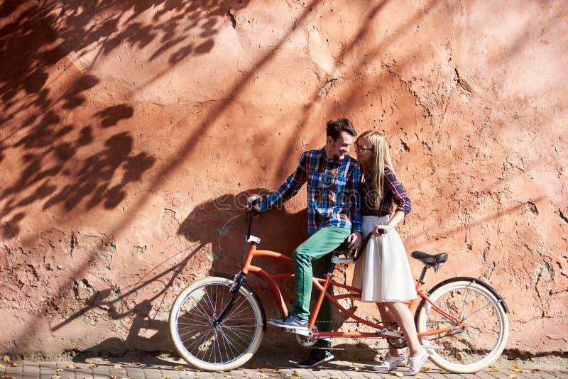 Os pares do turista, o homem farpado e a mulher loura na bicicleta em tandem no fundo do vermelho crepitaram parede foto de stock