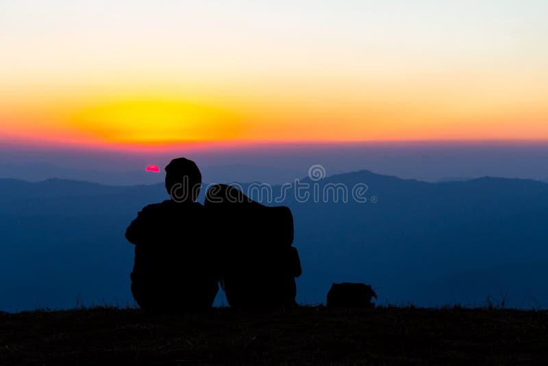 Os pares doces mostram em silhueta o assento na montanha com por do sol imagens de stock royalty free