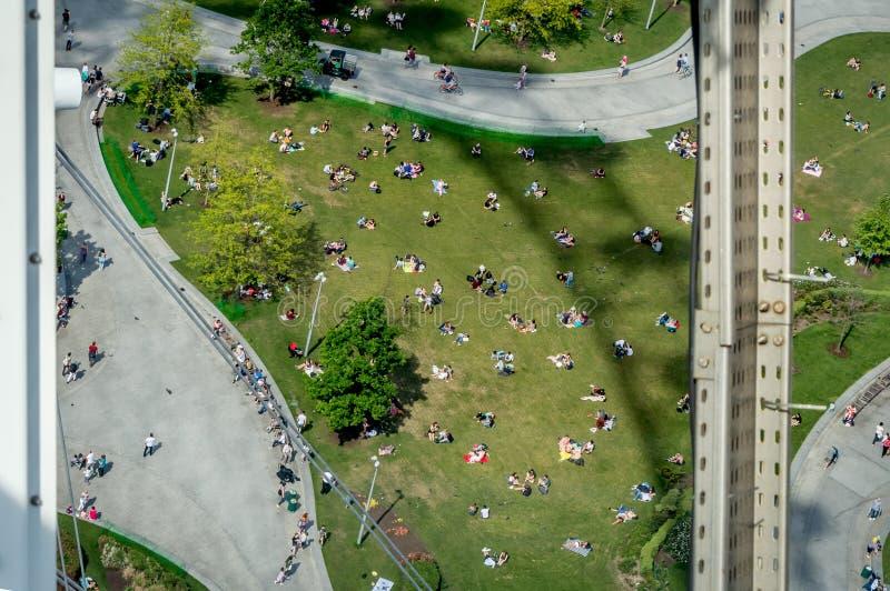 Os pares e as famílias que apreciam um fim de semana ensolarado bonito abaixo da Londres icónica eye imagem de stock