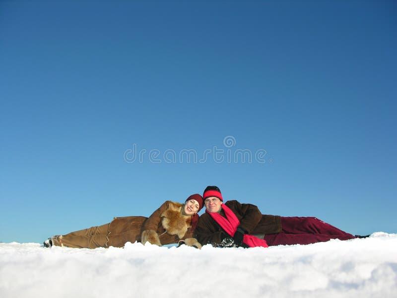 Os pares encontram-se na neve imagens de stock