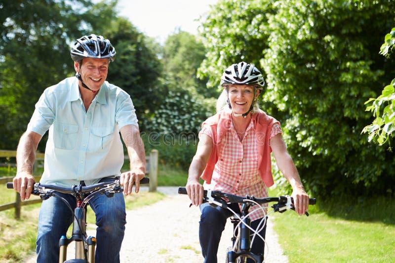 Os pares envelhecidos meio que apreciam o ciclo do país montam junto imagem de stock