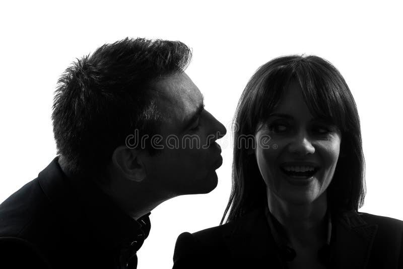 Os pares equipam o beijo da silhueta da mulher foto de stock