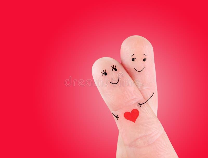 Os pares felizes abraçam o conceito, pintado nos dedos imagem de stock