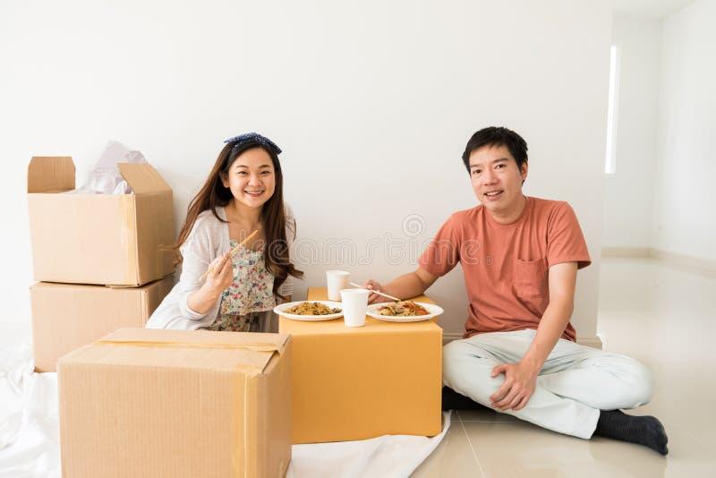 Os pares felizes comem o macarronete na caixa do carboard na casa nova fotografia de stock