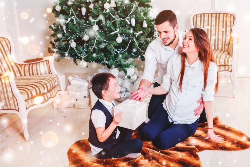 Os pares felizes da família dão presentes na sala de visitas, atrás da árvore de Natal decorada, a luz para dar uma atmosfera aco fotos de stock
