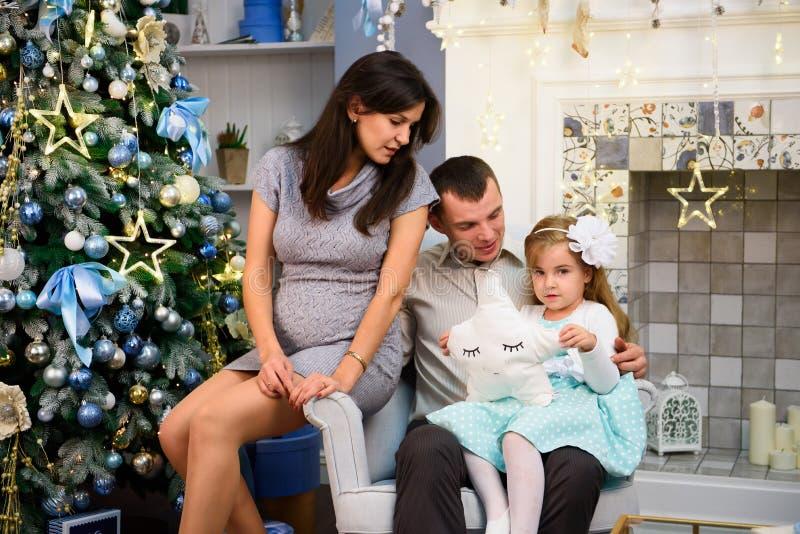 Os pares felizes da família dão presentes na sala de visitas, atrás da árvore de Natal decorada, a luz para dar uma atmosfera aco foto de stock