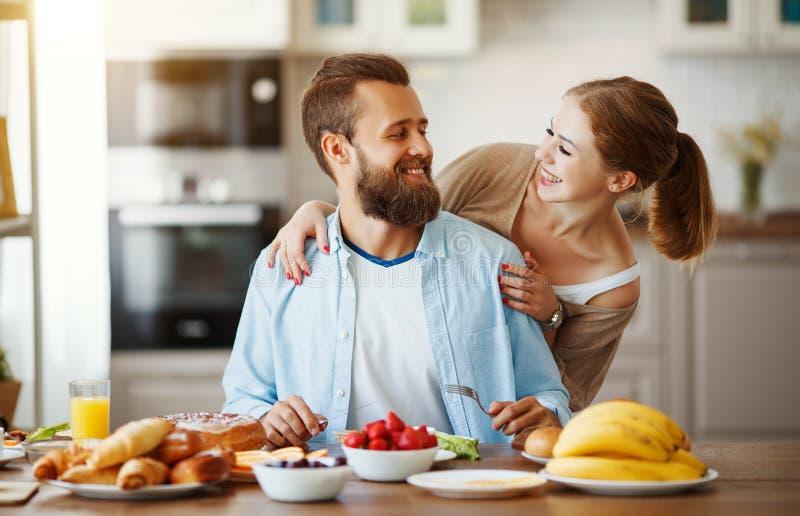 Os pares felizes da família têm o café da manhã na cozinha na manhã foto de stock royalty free