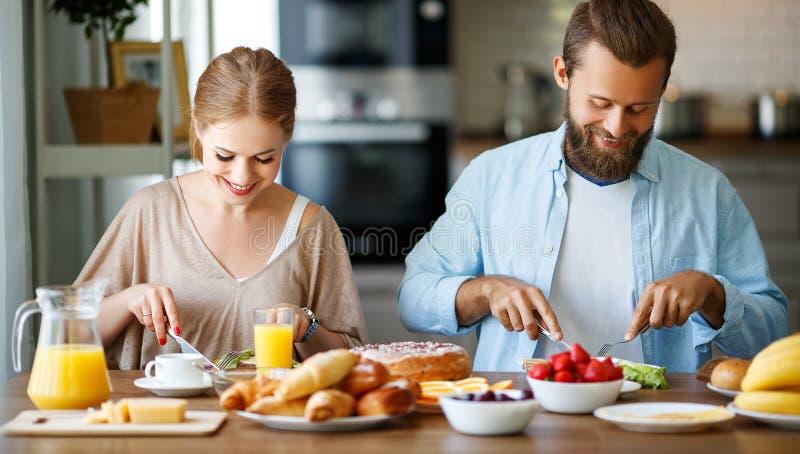 Os pares felizes da família têm o café da manhã na cozinha na manhã imagens de stock royalty free