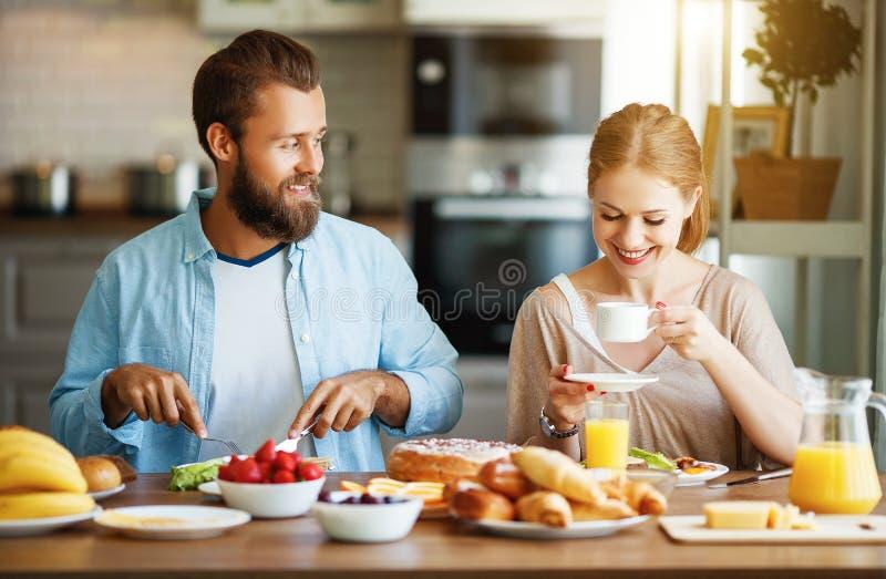 Os pares felizes da família têm o café da manhã na cozinha na manhã fotografia de stock royalty free