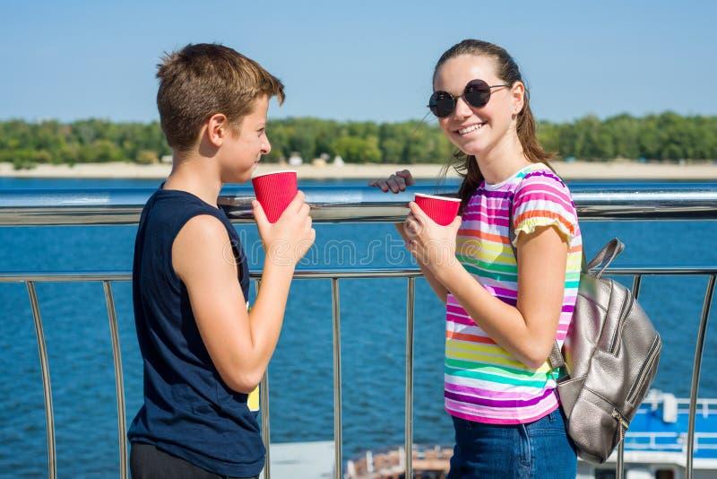 Os pares felizes de adolescentes estão andando, falando Terraplenagem da cidade do fundo foto de stock royalty free