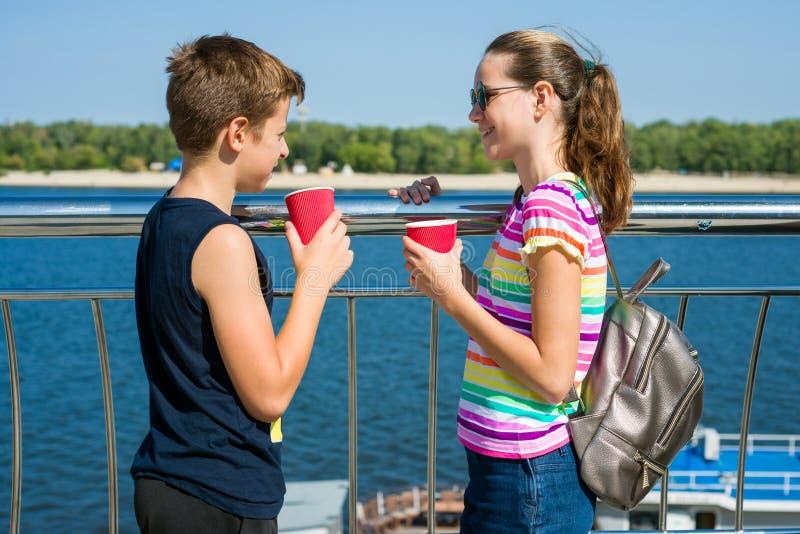 Os pares felizes de adolescentes são de passeio e bebendo o chá no ci fotos de stock