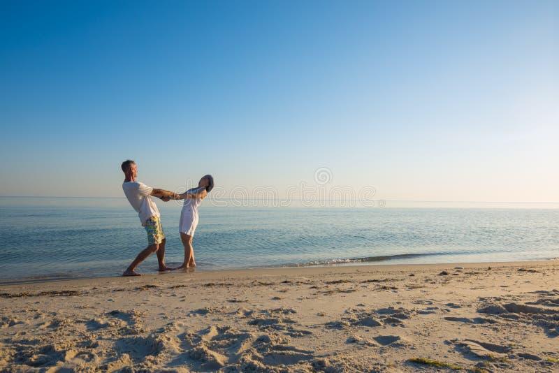 Os pares felizes de viajantes são girar, guardando as mãos fotos de stock royalty free