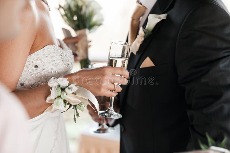 Os pares felizes dos recém-casados bebem o vinho branco do champanhe do casamento Cristais decorados Mãos dos noivos com ouro fotografia de stock