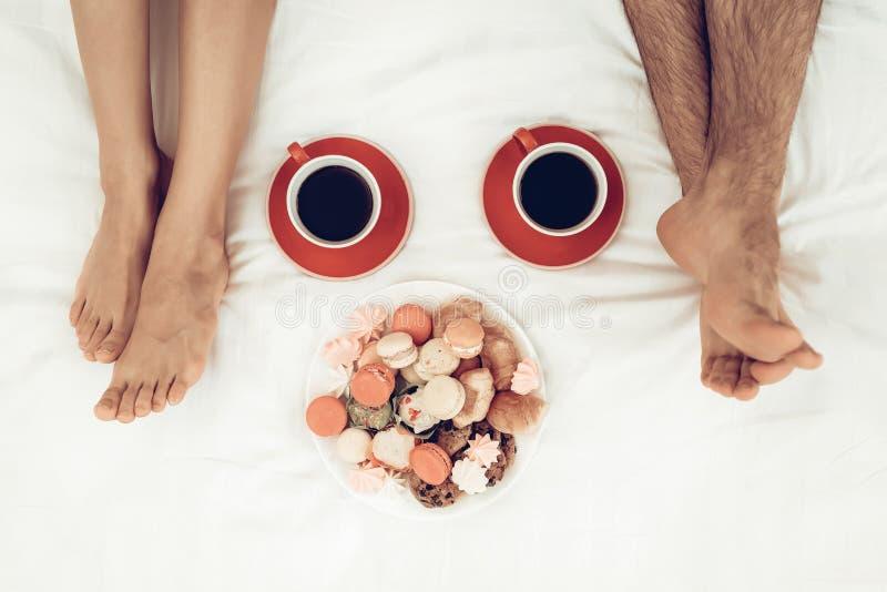 Os pares felizes estão encontrando-se na cama no dia do ` s do Valentim imagens de stock