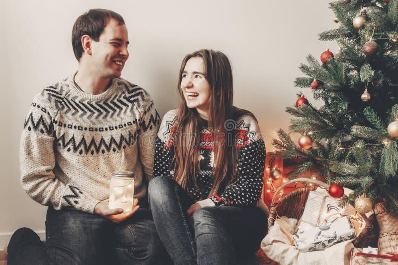 Os pares felizes nas camisetas à moda que guardam a lanterna iluminam-se no festiv fotos de stock
