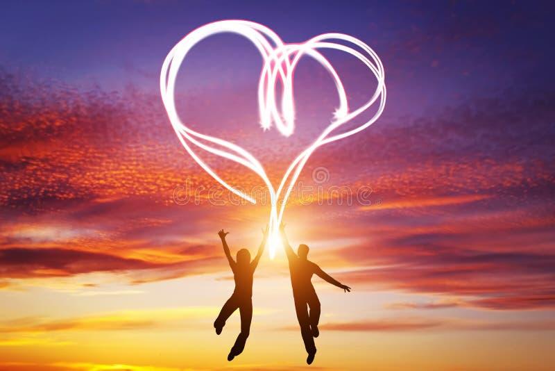 Os pares felizes no amor saltam fazendo o símbolo do coração da luz ilustração stock