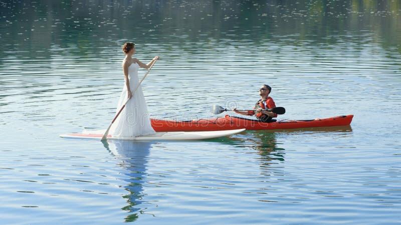 Os pares felizes no caiaque do esporte das férias SUP recém-casados foto de stock