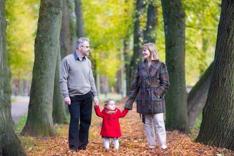 Os pares felizes no outono estacionam com menina da criança fotos de stock